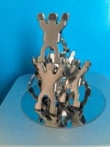 a team of metal models on a magnetic base, all stuck together in a pyramid to suggest teamwork