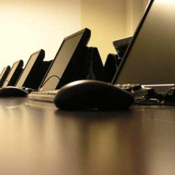 A row of perfectly set up computer stations in sepia
