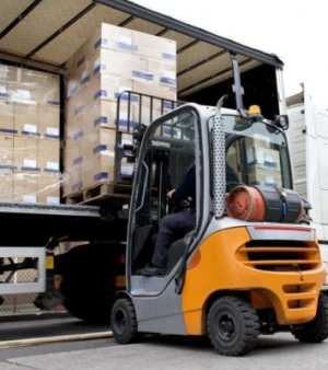 a fork lift truck unloading a lorry at a warehous