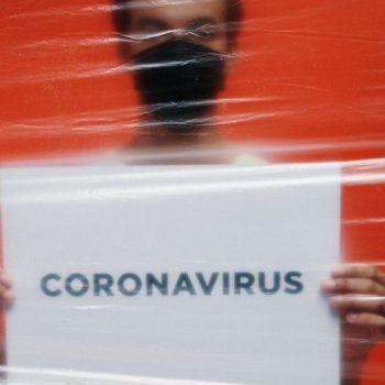 man holding a card with coronavirus written on it