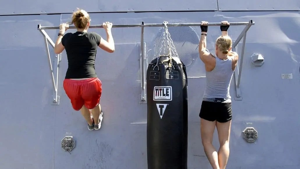 Two women doing a chin up and a pull up