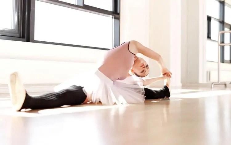 ballerina in leg warmers stretching