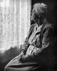 Elderly Lady pondering outside the window