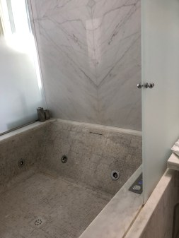 Deep tub covered in mosaic tile