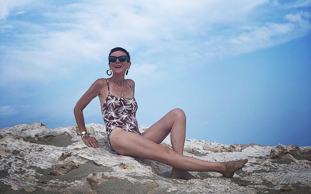 Frederique Gilain wearing Eres swimsuit and Celine earrings