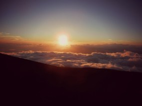 The sun sinks below the clouds during sunset at Haleakala.