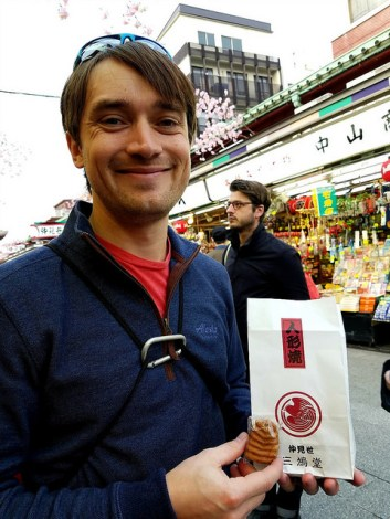 Author's boyfriend showing off a bag and a piece of ningyo-yaki.