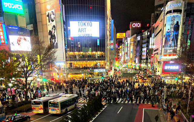 Watching dozens of people scramble through the intersection at the Shibuya crossing.