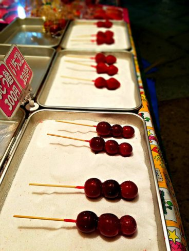 Candied fruit on a stick, on a bed of fine sugar.