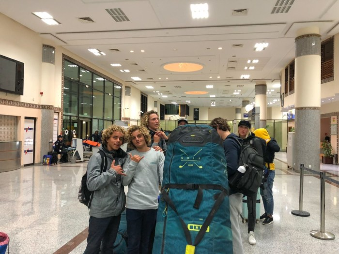 young travelers friends with giant luggage board bag kiteboarding travel