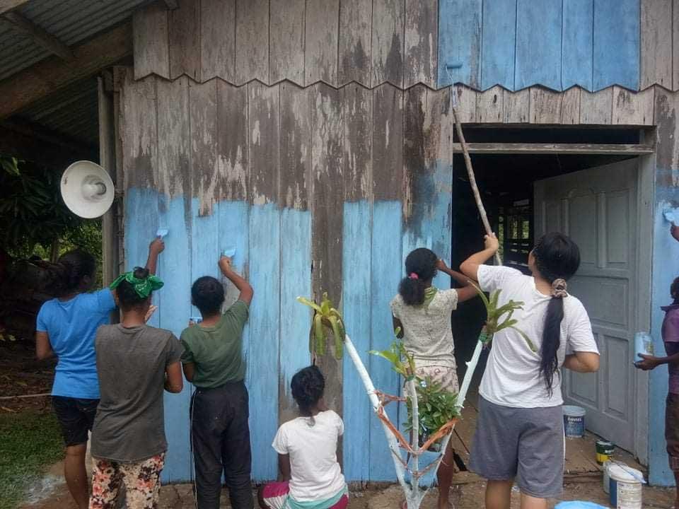 People paining a multi-purpose building
