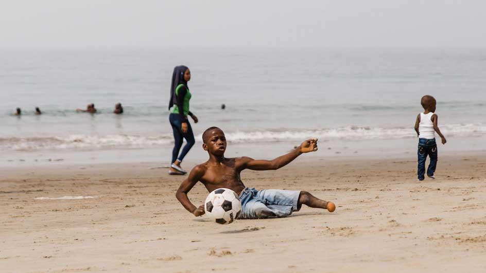 Ibrahim playing soccer on beach