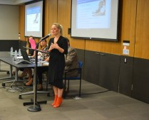 A woman in a black dress and bright orange heels speaks to the crowd, a captioned PowerPoint behind her