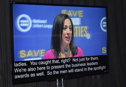 A woman in pink speaks to the audience, open captions below her