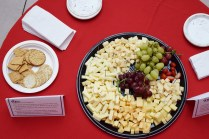 A large platter of cheese, grapes, and crackers sits on a table