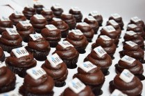 "Several rows of chocolate mini-cupcakes with ""WID"" on their frosting sit in a box"