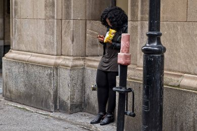 Girl with phone texting on the street