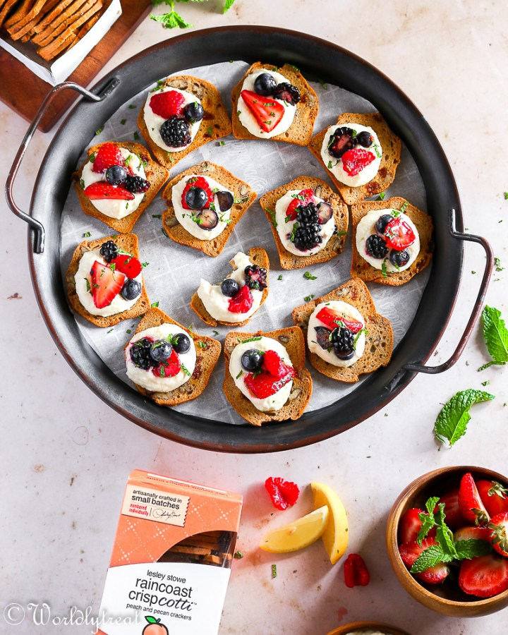A tray of cracker crisps with mascarpone and berries