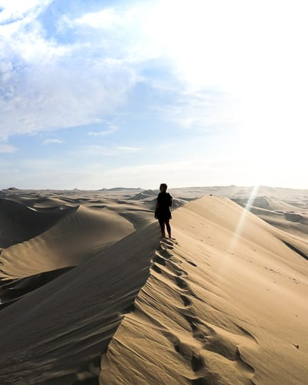 hiking to the top of huacachina dunes peru