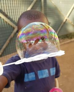 Child plays with bubble making toy at World Meets Kenya