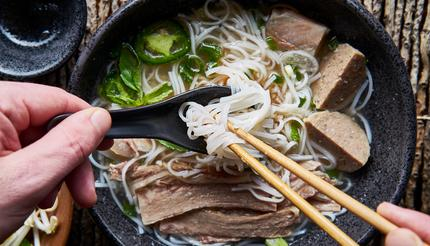 Eating pho with chopsticks and a spoon