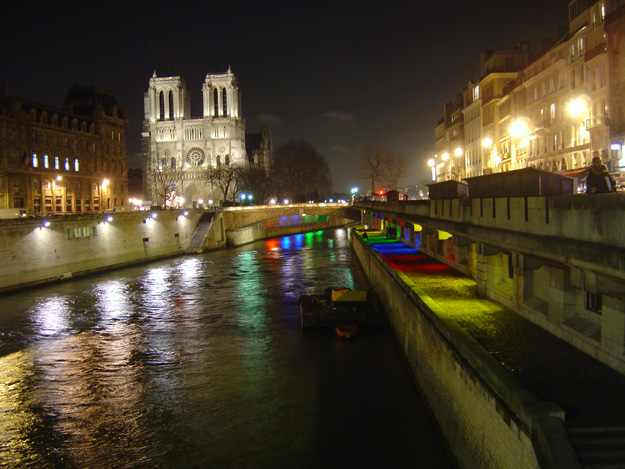 View of Notre Dame at night from the Seine in Paris, France