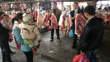 A family buying meat (open but from the baby again)
