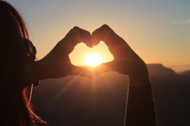 girl with sunglasses holding hands in shape of heart enclosing the sun at sunrise