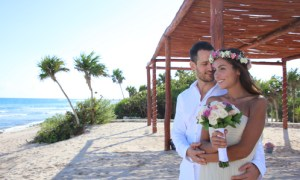 couple stands on the beach embracing. bride has a ring of flowers on her head and she holds a bouquet of pink, white and purple flowers. Palm trees decorate the beach.