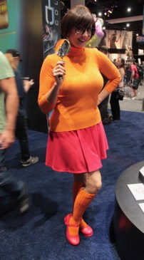 Darla from Scooby wearing orange poses with her magnifying glass