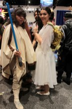 Princess Leia, gun drawn wearing a Yoda backpack standing next to her protector with light sabre