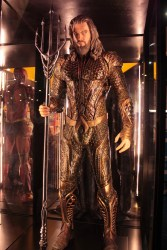 Auquaman in bronze and gold looking suit that looks scale patterned holding a trident with five points