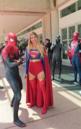 supergirl poses with the spidermen