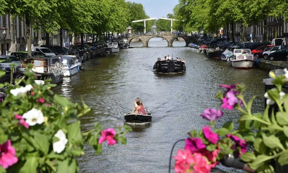 April city break ideas - Depicts Amsterdam's canals with colourful flowers