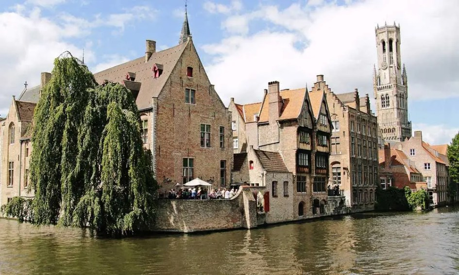 April city break ideas - depicts the river and quaint buildings of Bruges, Belgium