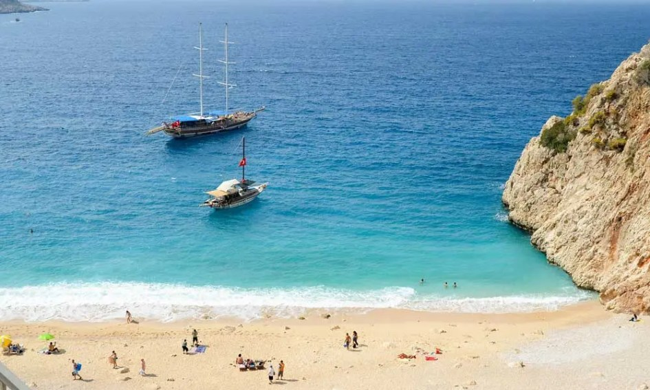Cheap July beach holidays - shows Antalya beach with a rock and two boats