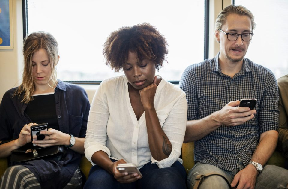 three people busy with their phone