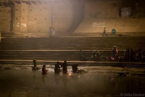 Hindu devotees bathing in the Ganges River before daybreak