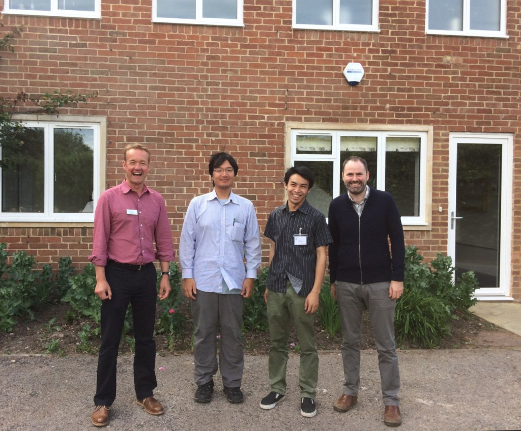 Four men smile outside redbrick house