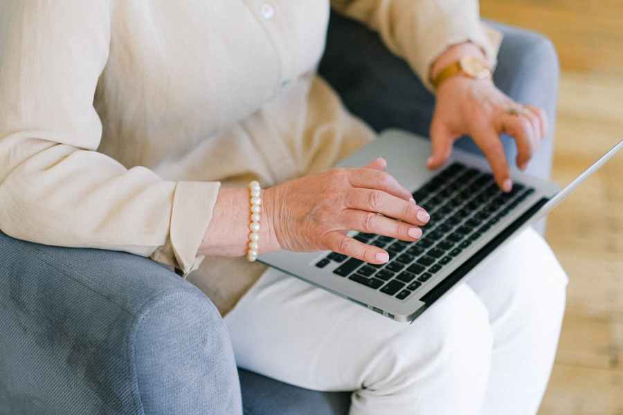 senior woman typing important report on keyboard of laptop