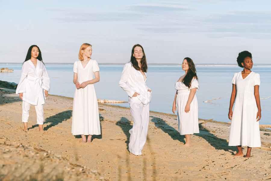 photo of women standing beside sea
