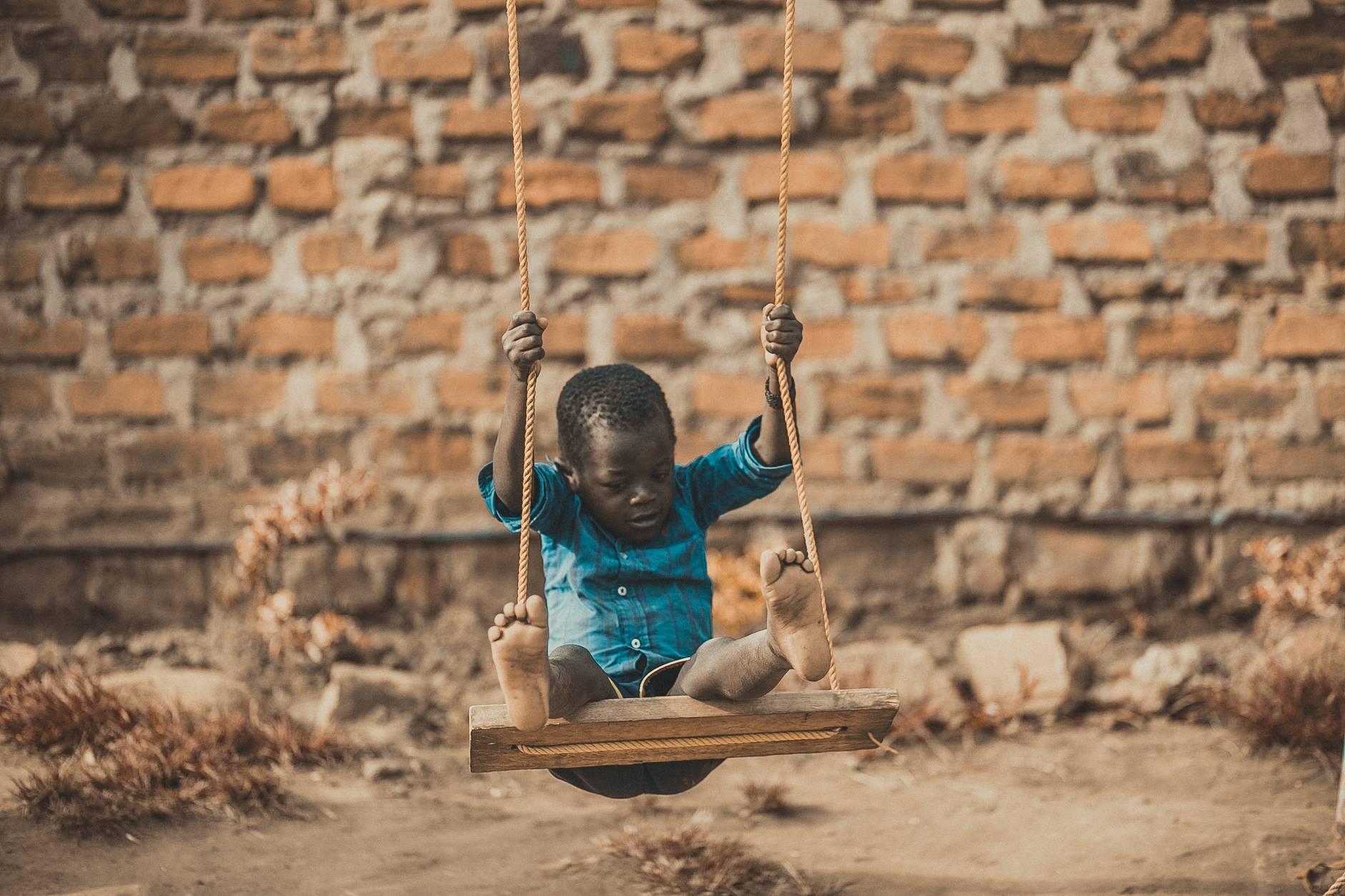boy wearing blue shirt sitting on swing