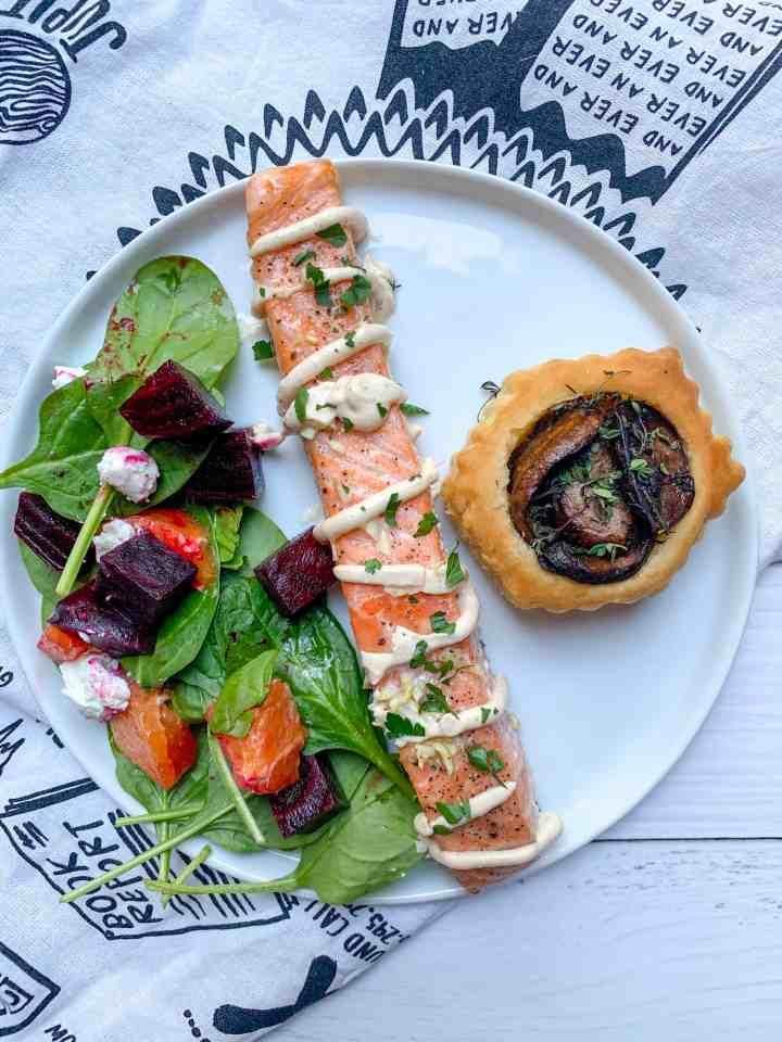 roasted salmon with yogurt tahini dressing, with a side salad and mushroom tart on a plate.