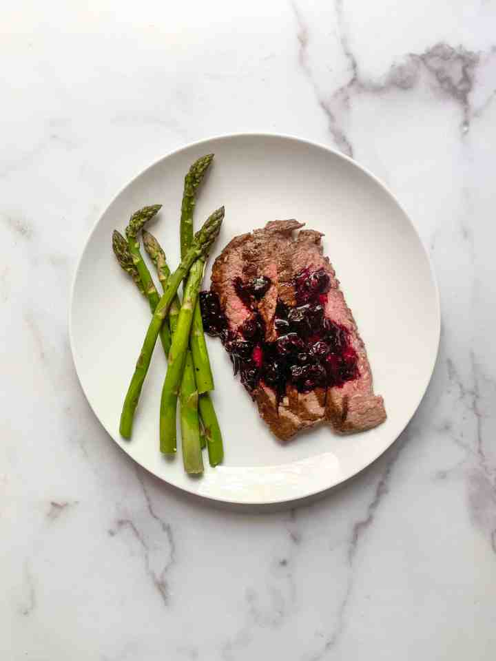 flank steak with blueberry balsamic sauce and asparagus