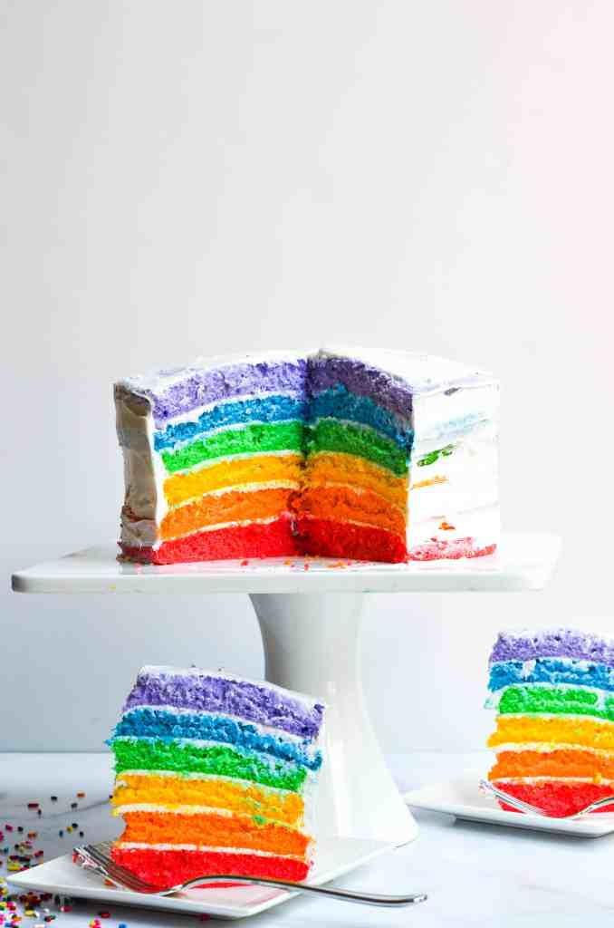 side view of rainbow cake on cake stand with two rainbow cake slices on smaller plates