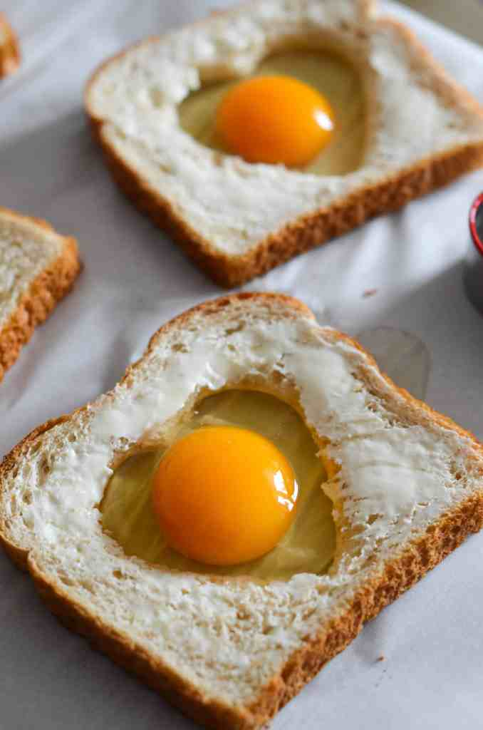 toasts are buttered before the eggs go in the hole to be baked.