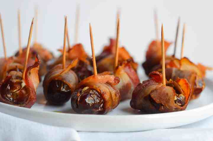 dates wrapped in bacon fully cooked on a white plate with toothpicks