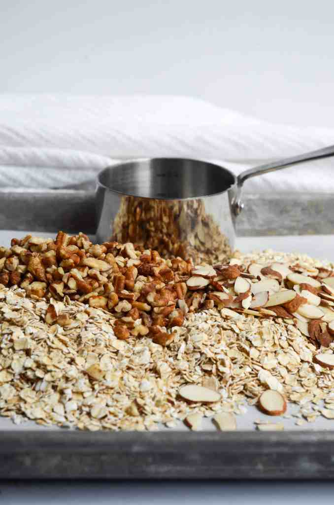 pecans, almonds and oats scattered around a sheet pan ready to be made into granola