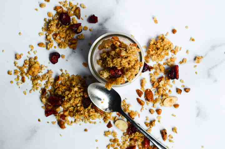 granola on top of a cup of yogurt with more granola loosely scattered around cup with spoon