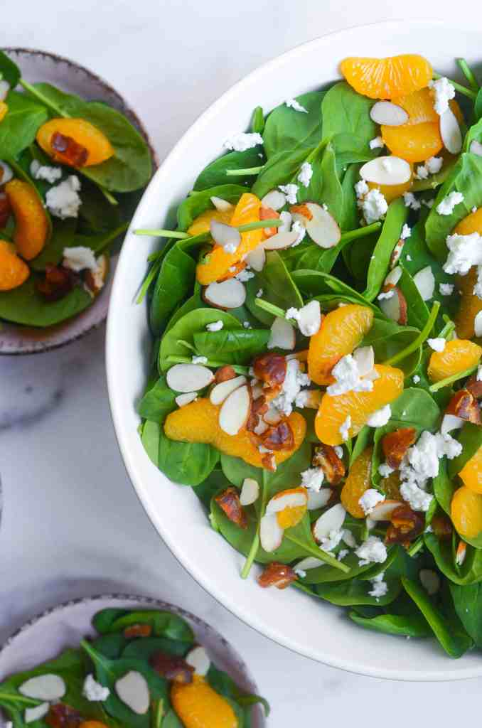 up close shot of spinach salad with mandarin oranges, dates, almonds, and goat cheese.